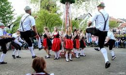 Volkstanzgruppe tanzt um den lebendigen Maibaum